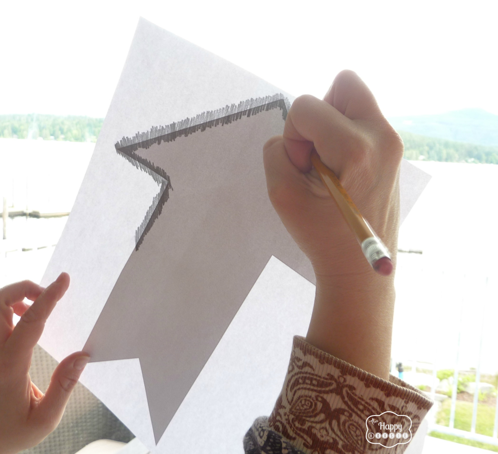 Tracing an arrow onto a stencil.