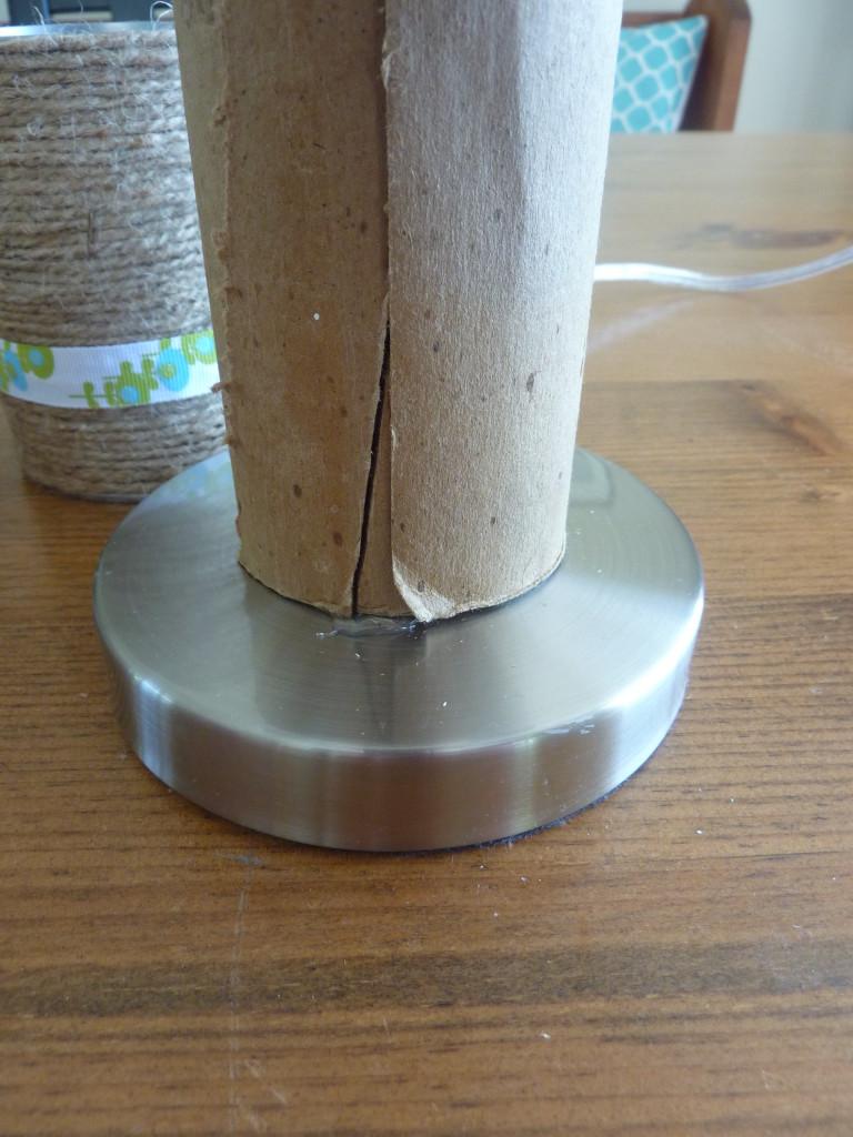 Using the hot glue gun to glue the cardboard to the base.