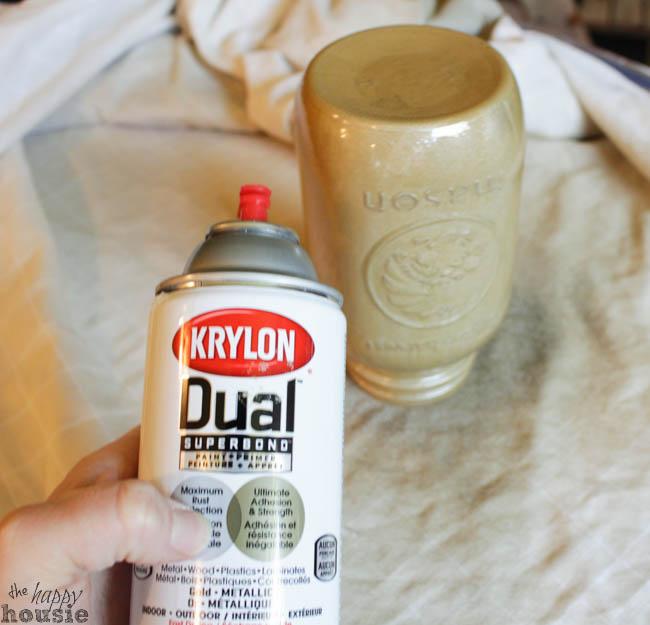Spraying the mason jar with gold spray.