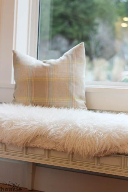 White faux fur is on a window seat.