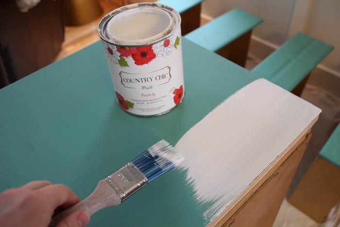 Using the paint brush to brush white paint on it.
