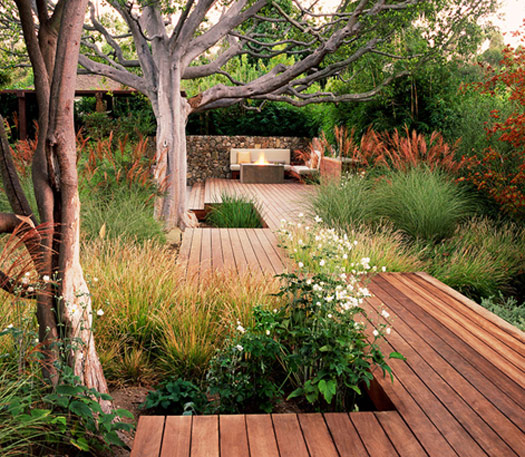 A panelled wooden deck with garden all around it.
