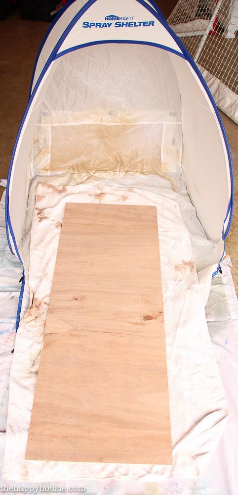 A wooden board in a spray paint shelfter.