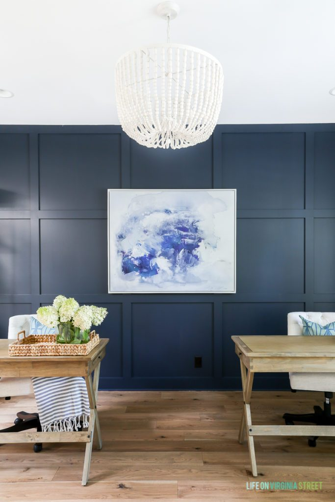 A dark blue wall panel behind desks in an office.