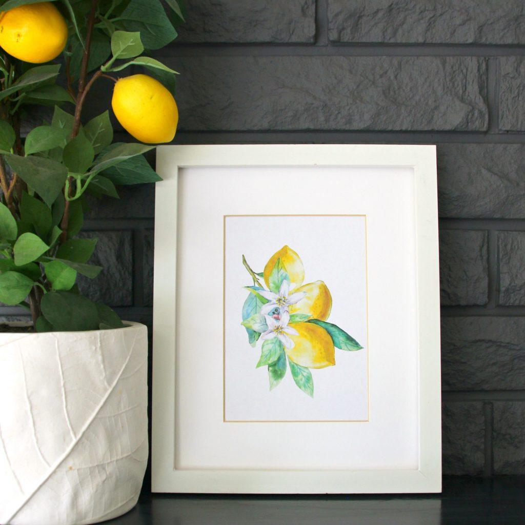 A white framed lemon print on the fireplace mantel.