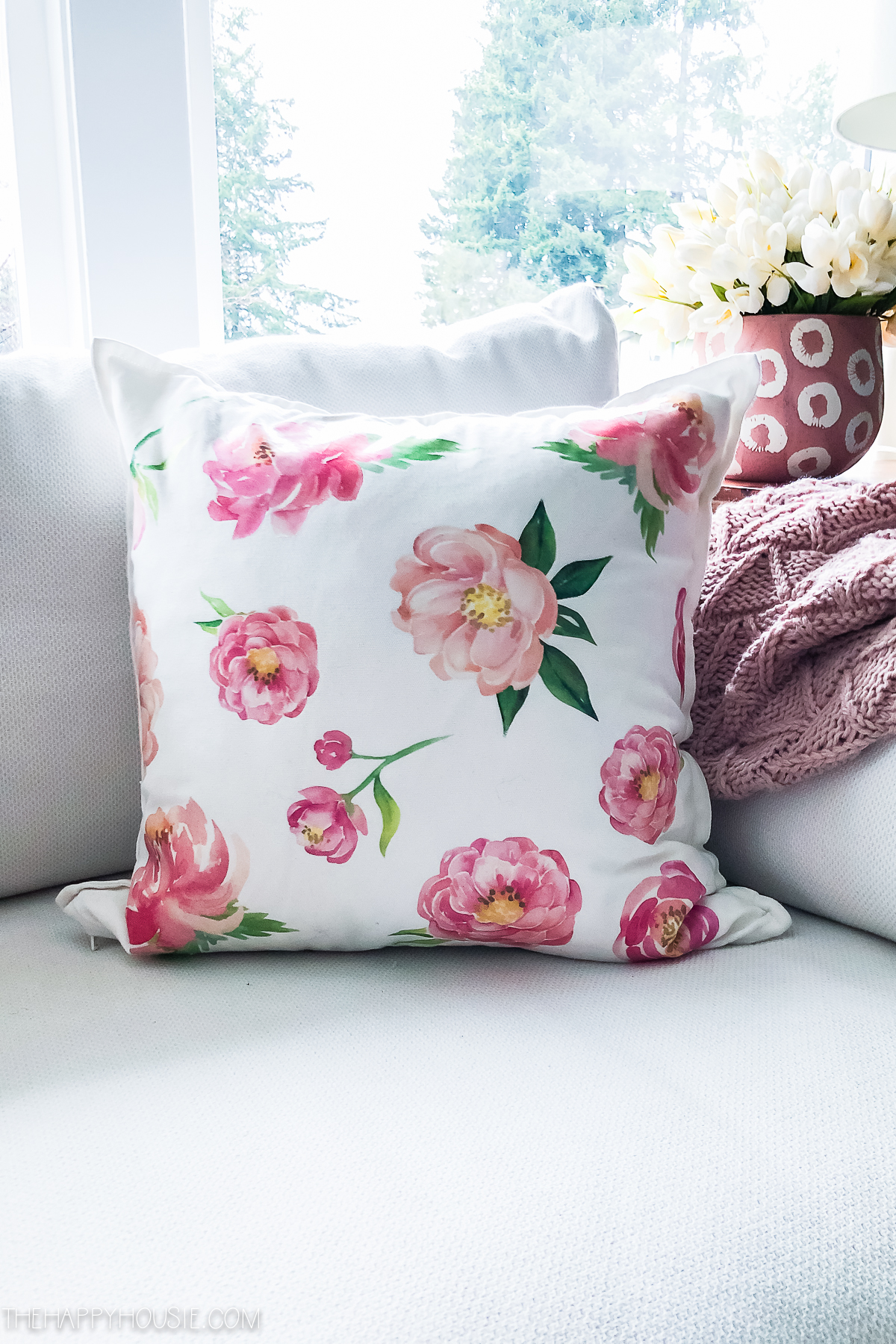 Floral pillow beside a pink throw.