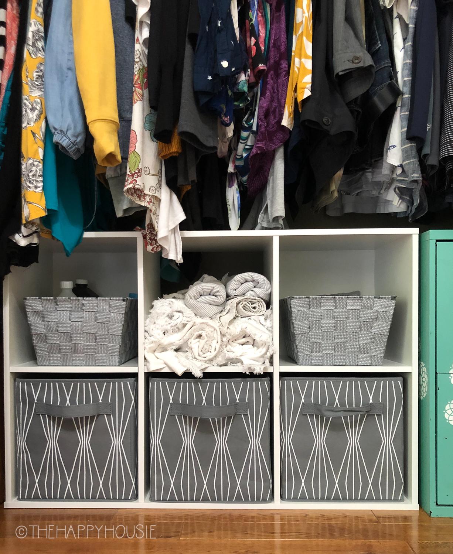 Organized bins on the bottom of the closet.